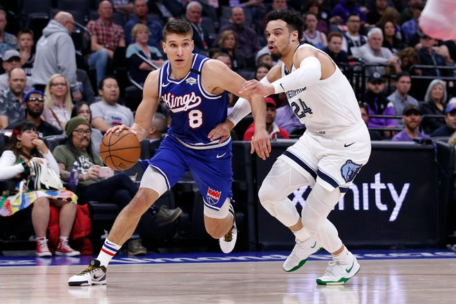 Sacramento Kings guard Bogdan Bogdanovic, left, drives to the basket against Memphis Grizzlies guard Dillon Brooks, right, during the first quarter of an NBA basketball game Thursday, Feb. 20, 2020, in Sacramento, Calif. (AP Photo/Rich Pedroncelli)