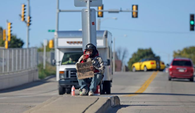 A man holds up a sign while in the middle of an intersection. The Wauwatosa Police Department fields calls every day for panhandling.