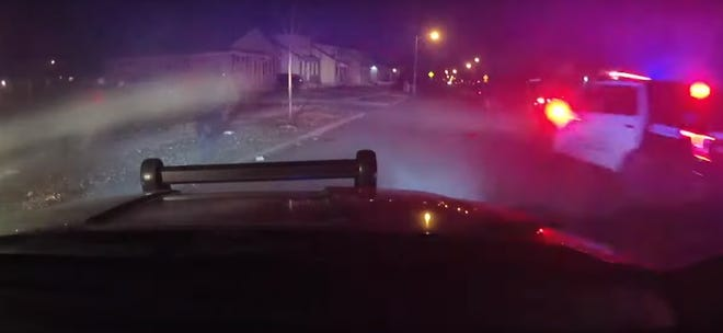 In the left corner of this image, the 23-year-old man Milwaukee police ultimately fatally shot raises his gun to fire at the officer standing to his right. The footage comes from a squad car's dashcam.