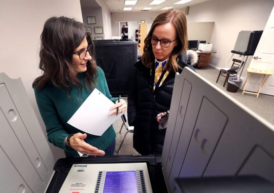 Election official Erica Sampson shows voter Lindsey Davenport the voting machine before Sampson votes early at the Rutherford County Election Office on Feb. 20, 2020.