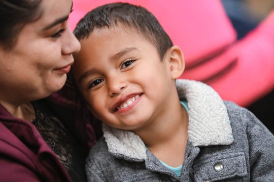 Cesar Gómez sits on his mother's lap at a migrant farmer resource fair in Hatch on Friday, Feb. 21, 2020.
