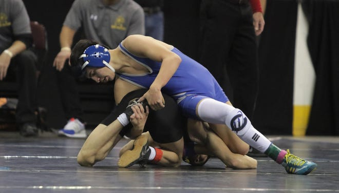 Carlsbad's Marcus Najera grabs the left foot of Hobbs' Daniel Leyva in a 5A 106-pound first-round match during Friday's New Mexico State Wrestling Championships at the Santa Ana Star Center in Rio Rancho.