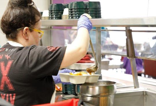 Ericka Babock drizzles gravy over potatoes, Wednesday, Feb. 19, 2020, while preparing food for Blanco Senior Center at Bloomfield Senior Center.