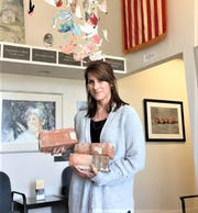 Plymouth Community Arts Council Director Lisa Howard holds bricks from the former Daisy Air Rifle factory that will be used in the sculpture.