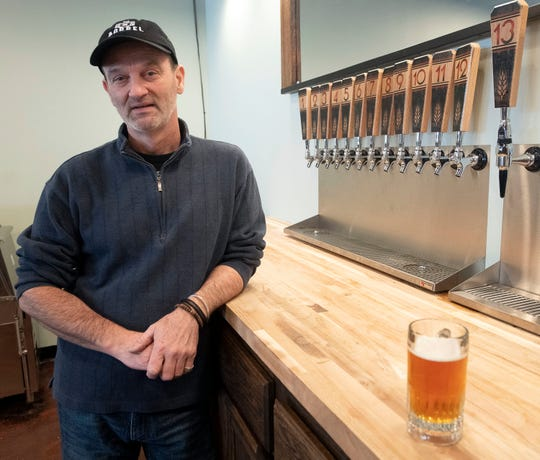 Tom Akin, owner of The 5 Barrel, stands for a photo after pouring a beer at the downtown Pensacola brewery and tap room.