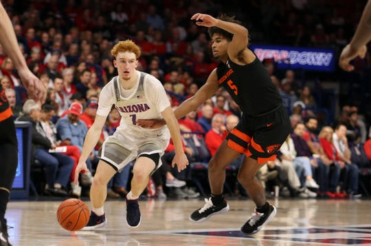 Feb 20, 2020; Tucson, Arizona, USA; Arizona Wildcats guard Nico Mannion (1) tries to dribble the ball past Oregon State Beavers guard Ethan Thompson (5) in the second half at McKale Center. Mandatory Credit: Jacob Snow-USA TODAY Sports