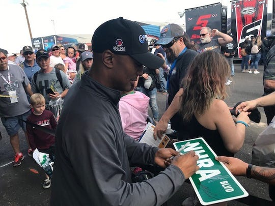 Antron Brown signs autographs for fans ahead of the 2020 NHRA Arizona Nationals