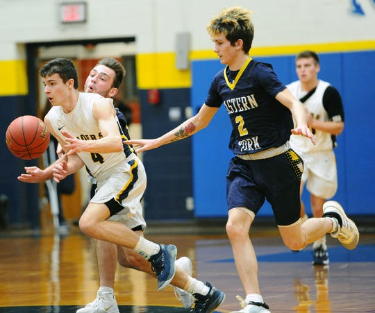 Elco's Bryce Coletti (4) drives up court between Eastern York's Kaleb Corwell (12) and Dustin Cunningham (2) during the first quarter of action.