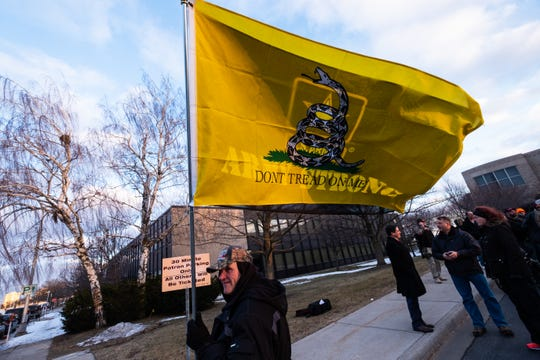 Robert Cowper, of Port Huron Township, waves a U.S. Army flag and a flag supporting the Second Amendment in the parking lot of the St. Clair County Admin Building before a Board of Commissioners meeting Thursday, Feb. 20, 2020.