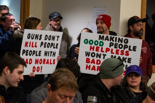 People in attendance of a St. Clair County Board of Commissioners meeting hold signs in support of the Second Amendment Thursday, Feb. 20, 2020, in the St. Clair County Admin Building. A crowd had gathered at the meeting to voice their opinions on a Second Amendment resolution passed by the county.