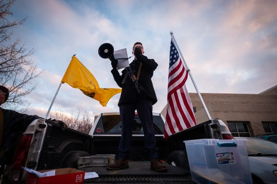 Dominic Jakubowski holds his rifle while addressing a crowd through a megaphone in the parking lot of the St. Clair County Admin Building before a Board of Commissioners meeting Thursday, Feb. 20, 2020. A crowd had gathered at the meeting to voice their opinions on a Second Amendment resolution passed by the county.