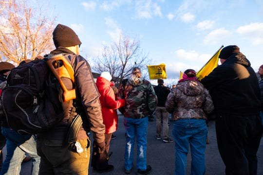 James Empey, of Marine City, carries his AK-47 as he joins others in gathering in the parking lot of the St. Clair County Admin Building before a Board of Commissioners meeting Thursday, Feb. 20, 2020.