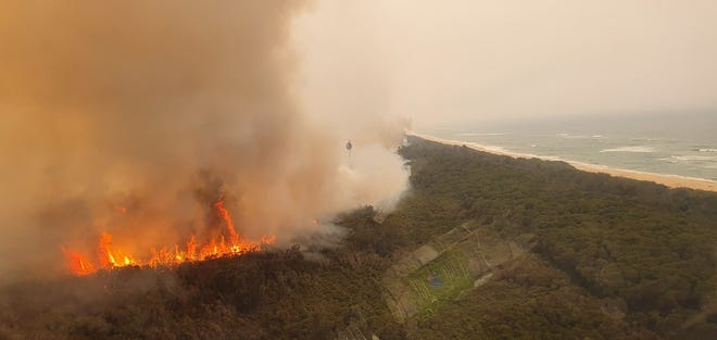 A helicopter, used for fire suppression efforts, flies overhead of a large blaze in Australia in January 2020.