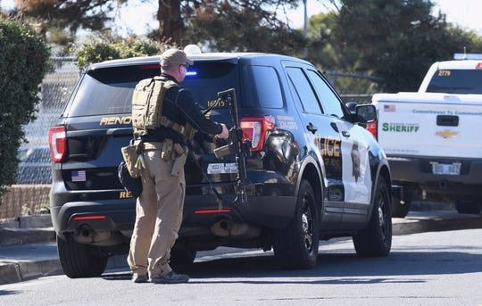 Law enforcement officers are seen holding their weapons as they respond to a report of gunfire Friday, Feb. 21, 2020, on Stardust Street and Stoker Avenue in Reno.