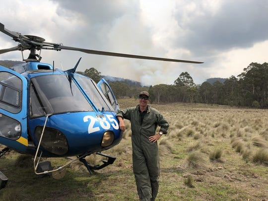 A photo of Justin Cutler standing next to a helicopter in New South Wales.