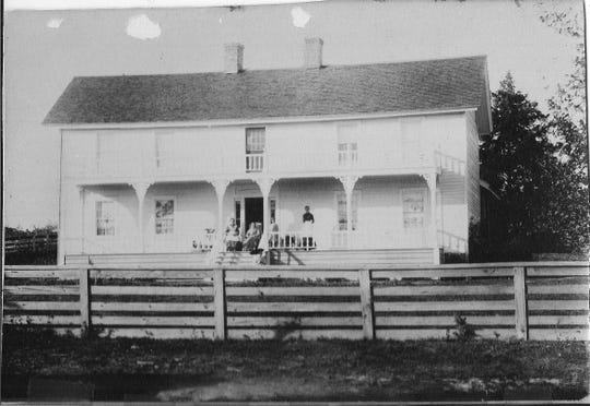 An early photograph of the pioneer homestead Brunk House. The house was built by Harrison and Emily Brunk in 1861. Emily is seated directly in front of the door.