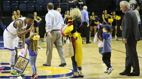 Angelo State University's Collin Turner gets a high-five from a Rams fan after scoring a career-high 44 points in a win against Texas A&M-Kingsville earlier in the season in San Angelo as ASU president Brian May joins in.