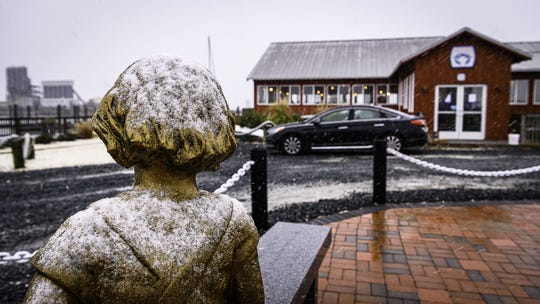 The first snow of the year begins to coat the Waterman's Memorial at the Cape Charles Town Marina on Thursday