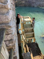 Volunteers rebuild a water wheel on the mill at what was the former Dogpatch USA.