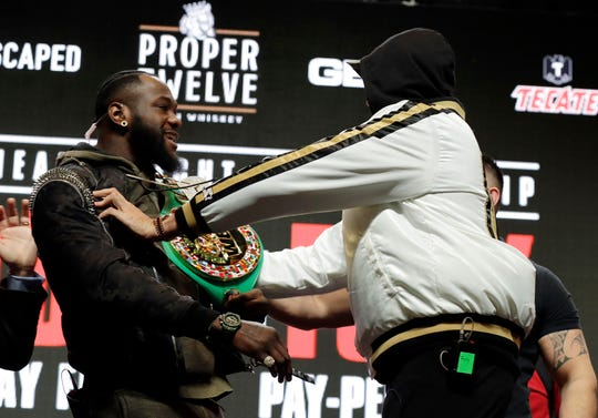 Tyson Fury, of England, right, shoves Deontay Wilder Wednesday, Feb. 19, 2020, in Las Vegas during a faceoff for photographers at a news conference for their upcoming WBC heavyweight championship boxing match.