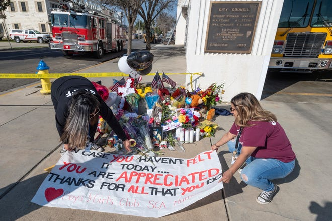 Gaby Carbajal, left, and Patty Diaz place a banner Thursday, February 20, 2020 made by students at the Boys & Girls Club. Many have left flowers and notes in memory of the two firefighters lost in Tuesday's fire at the Porterville library.