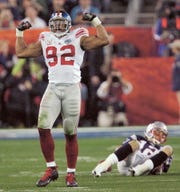 New York Giants defensive end Michael Strahan reacts after sacking New England Patriots quarterback Tom Brady during Super Bowl XLII on Sunday, Feb. 3, 2008 in Glendale, Ariz.