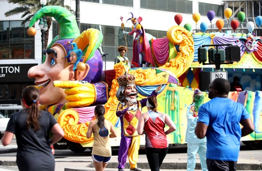Participants run by a Mardi Gras float during the 2020 Rock 'n' Roll New Orleans Marathon in New Orleans.