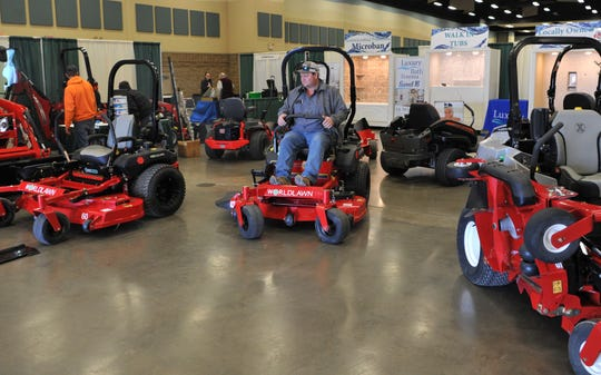 Vieth Tractor & IMP's Trey Veitenheimer arranges heavy mowing equipment Friday morning for their booth at the annual Arts Alive Home and Garden Festival event held at the Wichita Falls MPEC.