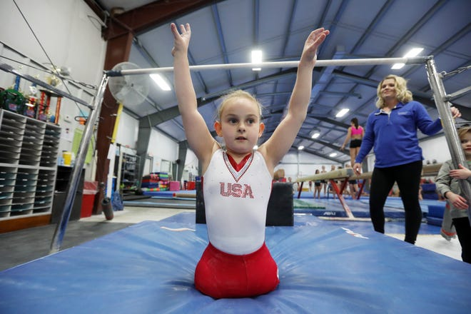 Paige Calendine finishes her bars routine during practice at Zanesville Gymnastics on Thursday. Calendine, 8, will compete in a gymnastics meet this weekend.