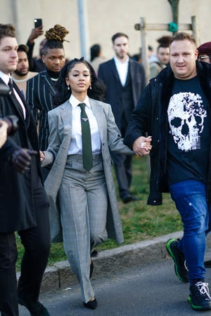 Saweetie wears a gray jacket, earrings, a white shirt, a tie, outside Prada, during Milan Fashion Week Fall/Winter 2020-2021 on Feb. 20, 2020.