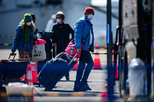 Mask-clad passengers prepare to board a bus after disembarking from the Diamond Princess cruise ship, in quarantine due to fears of new COVID-19 coronavirus, at Daikoku pier cruise terminal in Yokohama on Feb. 21, 2020. Hundreds of people have been allowed to leave the ship after testing negative for the disease and many have returned to their home countries to face further quarantine.