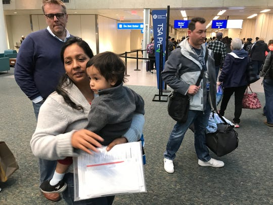 Vilma Diaz holds her 2-year-old son Josue before being taken through security at Orlando International Airport on Feb. 22.