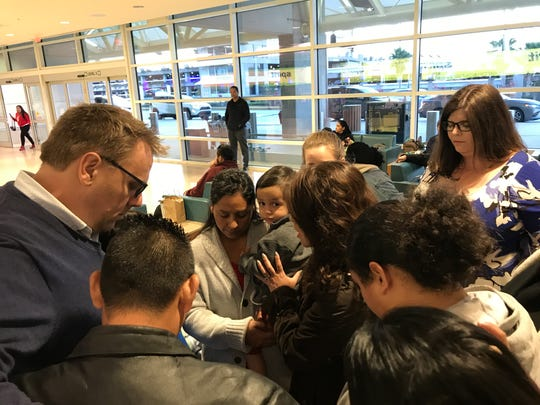 Vilma Diaz prays with friends and family before being deported to El Salvador at the Orlando International Airport on Feb. 22.