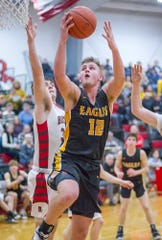 Colonel Crawford's Gavin Feichtner finishes at the basket past Buckeye Central's Brady Kerschner.