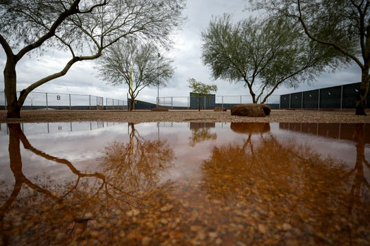 Water pools after rainfall as the Cincinnati Reds were forced indoors for their spring practice, Saturday, Feb. 22, 2020, at the baseball team's spring training facility in Goodyear, Ariz. The rain canceled the first spring game of the season between the Cincinnati Reds and Cleveland Indians.