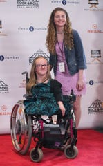 """Lindsay O'Keefe of Lakewood, Ohio, top, and Breanna Sprenger of Avon, Ohio, walk the red carpet during the fourth annual """"Kids Film It Festival"""" at the Rock & Roll Hall of Fame and Museum on Friday, Feb. 21, 2020, in Cleveland, Ohio."""