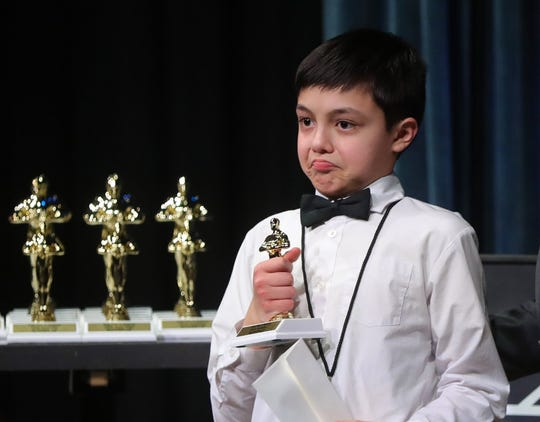 """Charlie Haffke of Shaker Heights, Ohio, gives a slight pout as he accepts the runner-up trophy in the 8-11-year-old animation category for his film """"Noise is Overrated"""" during the fourth annual """"Kids Film It Festival"""" at the Rock & Roll Hall of Fame and Museum on Friday, Feb. 21, 2020, in Cleveland, Ohio."""