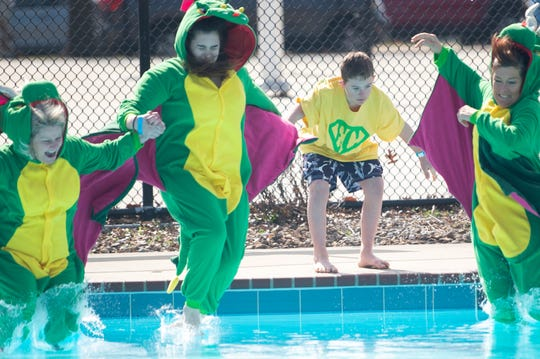 Sam Baker stays behind as Lori Speich, Madison Piche and Kellie Piche (from left) jump into the pool during the Special Olympics Tennessee Polar Plunge at Austin Peay State University Saturday, Feb. 22, 2020, in Clarksville, Tenn.