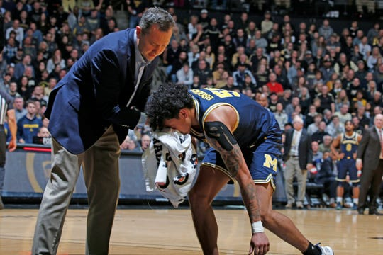 Michigan guard Eli Brooks has a nose bleed and gets helped off the floor against Purdue during the second half of U-M's 71-63 win on Saturday, Feb. 22, 2020, in West Lafayette.