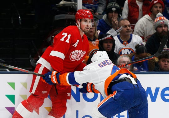 New York Islanders defenseman Andy Greene and Detroit Red Wings center Dylan Larkin come together at the boards during the first period Feb. 21, 2020 in Uniondale, New York.