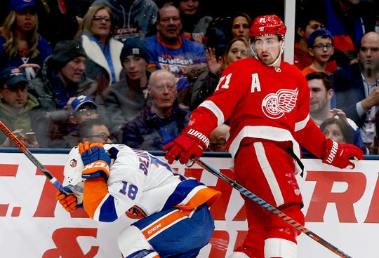 Feb 21, 2020; Uniondale, New York, USA; New York Islanders left wing Anthony Beauvillier (18) holds his head after being elbowed by Detroit Red Wings center Dylan Larkin (71) during the first period at Nassau Veterans Memorial Coliseum.