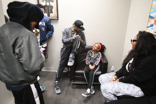 "Rapper and songwriter Royce da 5'9"", Ryan Montgomery,  jokes around with his daughter Lyric Montgomery, 11 in a backstage dressing room with his wife Artegia Montgomery and friends and family before his set."
