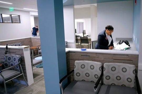 In this Oct. 2, 2019, file photo, Anita Murphy, a Planned Parenthood executive, does paperwork in the waiting room during a media tour of the new Fairview Heights, Ill., facility prior to open that month. Illinois is among several states picking up the tab in 2020 for family planning services at clinics run by Planned Parenthood, which quit participating in the federal funding program in 2019.