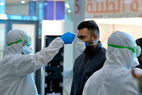 FILE - In this Friday, Feb. 21, 2020, file photo, medical staff check passengers arriving from Iran in the airport in Najaf, Iraq. Coronavirus-infected travelers from Iran already have been discovered in Lebanon and Canada.