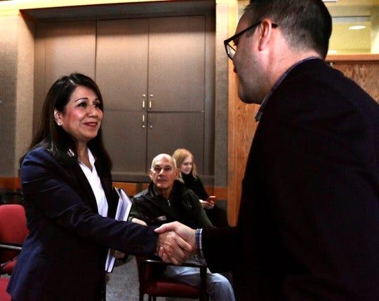 Mayor Michael Fournier greets city manager candidate Jane Bais DiSessa, left, Pontiac's deputy mayor.