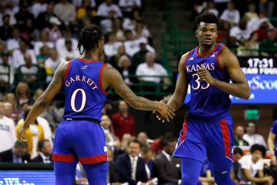 Kansas center Udoka Azubuike, right, low fives guard Marcus Garrett, left, after a made basket against Baylor during the second half.