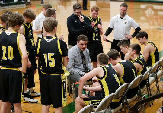 Waupun High School boys basketball coach Brett Pickarts talks to his team during a timeout in a game against Berlin on Feb. 21 in Berlin.