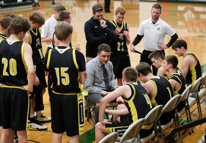 Waupun High School boys basketball coach Brett Pickarts talks to his team during a timeout in a game against Berlin on Feb. 21 in Berlin.