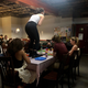 Madeline Bonahue stands up on a table and shouts at Lillie Brody during the dinner scene of the performance.