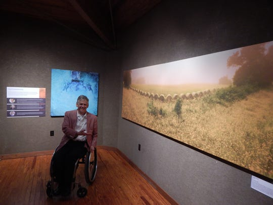 """Max Lee, one of the three artists that make up The Wheelchair Highwaymen, poses excitedly beside one of their photos, """"Bellamy Gold,"""" an area which, today, """"is largely I-10."""""""